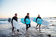 Father and son walking out of the water after their surf at St Ouen's Bay, Jersey, CI at sunset, enjoying their healthy surfing lifestyle.