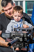 A father shows his boy a large machine gun on the Royla Anglians stand - Duxford Battle of Britain Air Show at the Imperial War Museum. Also commemorating the 50th anniversary of the 1969 Battle of Britain film. It runs on Saturday 21 & Sunday 22 September 2019