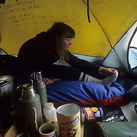 Julie Hanson stretches in tent before a long day of mushing on Arctic Ocean.