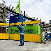 """Nederland Rotterdam 3 september 2007 20070903 .Voorbijganger/ man fotografeert het voormalige centraal station., wat op het punt staat gesloopt te worden. Op de gevel van het oude (vertrouwde) pand hangt het doek """" Het doek is gevallen """" Binnenkort zal het pand het definitief gesloopt worden.  ."""" Het doek is gevallen """" Zondag 2 september is het doek letterlijk doek gevallen voor het in 1957 geopende gebouw. Over enkele weken wordt de schepping van architect Sybold van Ravesteyn gesloopt en komt op het Stationsplein een nieuwe OV-terminal, die na 2011 ruim 300.000 reizigers per dag moet kunnen verwerken. Voorbijgangers maken een foto van het oude bekende centraal station, dat sinds 1957 dienst heeft gedaan. Een gloednieuw station zal op deze plek verrijzen. Op de achetrgrond links het tijdelijke centraal station. ..Het tijdelijke station dat de periode overbrugt tussen de sloop van het oude Rotterdam CS en de bouw van een nieuw station, kost 12 miljoen euro. Dat is een schijntje vergeleken met het half miljard waarop het nieuwe is begroot. De bedoeling is dat de tijdelijke bebouwing in februari klaar is. Het blijft open tot 2010. Het oude gebouw maakt plaats voor vijf tijdelijke. Daarvan zijn er vier voor de reizigers en een voor het personeel van de Spoorwegpolitie. ..Tijdelijk Rotterdam Centraal.1 september 2007..Alle treinreizigers opgelet! Vanaf 2 september sta je voor een dichte deur als je bij Rotterdam Centraal op de trein wilt stappen. Tenzij je de ingang van het tijdelijke Rotterdam Centraal al gevonden hebt. ..Naast het oude vertrouwde station staat al een tijdje een groot blauw gebouw en vanaf 2 september kun je daar op je trein stappen. Je kunt er zelfs een kopje koffie halen, of kleine boodschappen doen. Alle winkels zijn namelijk gewoon verplaatst naar het grootste tijdelijke station van Nederland...Het Centraal Station was al een hele tijd een grote bouwput, want er wordt heel hard gewerkt aan een nieuw, beter en vooral moderner station. Maar omdat afs"""