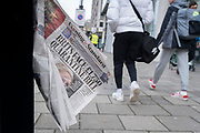 As pedestrians walk past, an old copy of yesterday's Evening Standard newspaper blows in the wind as, still carrying the headline about the government's decision to quarantine and test air travellers flying into the UK, during the third lockdown of the Coronavirus  pandemic, in the City of London, the capital's financial district, on 10th February 2021, in London, England.