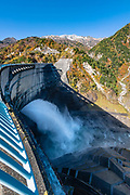 Kurobe Dam is Japan's tallest dam at 186 meters / 610 ft. Built with many difficulties over 7 years, it was completed in 1963. Over 170 people lost their lives to the project. Its hydropower plant supplies electricity to the Kansai Region. Kurobe Dam spans across Kurobe Lake in an arc, and it can be accessed via electric bus from the east or the cablecar from the west. Visitors walk over the dam to get between the bus and cablecar stations in about 10-15 minutes. At the eastern end of the dam, a long flight of stairs leads up the concrete-covered mountain slope for an aerial view of the dam and its surroundings. The Tateyama Kurobe Alpine Route carries visitors across the Northern Japan Alps via cablecars, trolley buses and a ropeway. Completed in 1971, this transportation corridor connects Toyama City in Toyama Prefecture with Omachi Town in Nagano Prefecture. The Tateyama Mountain Range lies within Chubu Sangaku National Park. This image was stitched from multiple overlapping photos.