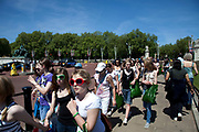 Young tourists wearing sunglasses outside Buckingham Palace on a sunny spring day in London. This is a very busy area for tourism due to all the Royal architecture, gardens and statues.