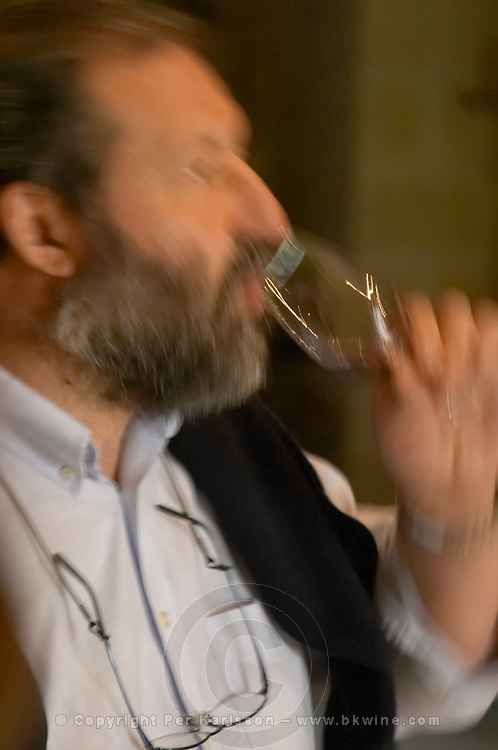 In the wine tasting room, Pascal Delbec, owner and wine maker holding a glass and tasting his wine motion blur Chateau Belair (Bel Air) 1er premier Grand Cru Classe Saint Emilion Bordeaux Gironde Aquitaine France