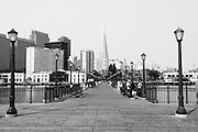 A black and white image looking down a pier towards downtown San Francisco.