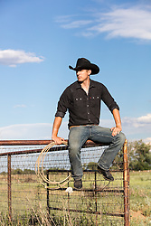 All American Cowboy sitting on a fence