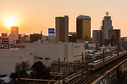 A commuter train passes through urban Tokyo at sunset with the towers of the Asahi Beer Hall in Asakusa behind . Tokyo, Japan Friday, February 5th 2011