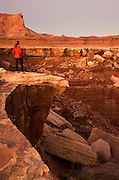 Hiker looks into the canyon along the White Rim Trail, Island in the Sky District, Canyonlands National Park, near Moab, Utah.  (model released)
