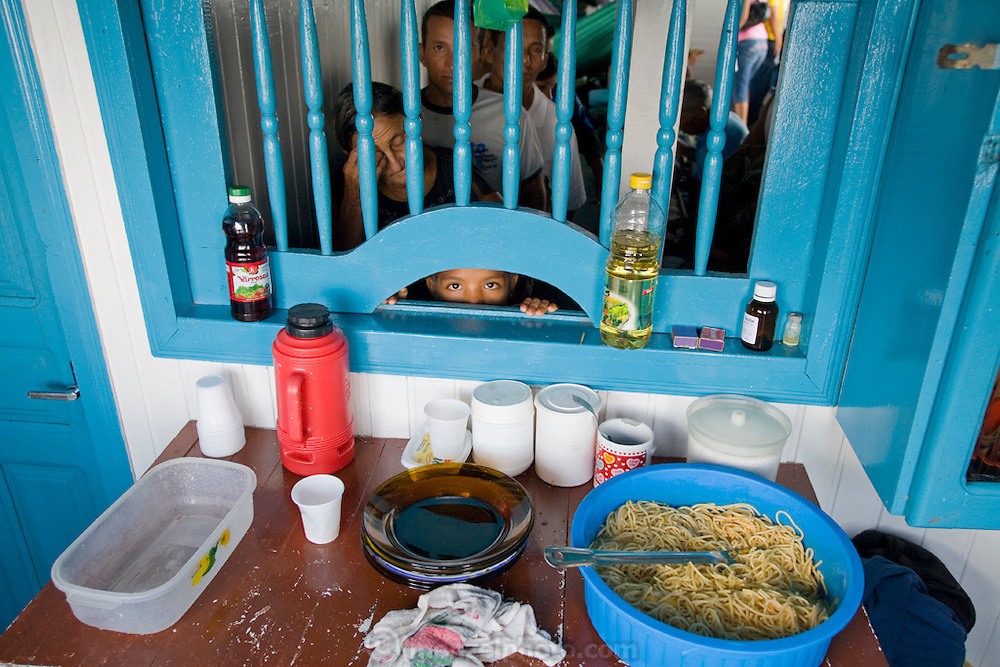 Customers line up for a noodle dish aboard a boat in Mancapuru, Brazil.