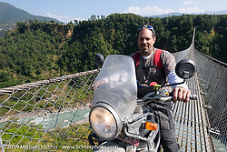 Jason Adamski riding over the Kushma - Gyadi suspension bridge over the Modi River (the highest, at 384 feet, and longest, at 1,128 feet, suspension bridge in Nepal) during Motorcycle Sherpa's Ride to the Heavens motorcycle adventure in the Himalayas of Nepal. On the sixth day of riding, we went from Tatopani to Pokhara. Saturday, November 9, 2019. Photography ©2019 Michael Lichter.