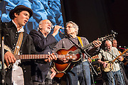 Peter Yarrow, holding the mic, leads in a song as Happy Traum plays guitar beside him. On the far right, playing banjo, is Pete Seeger.