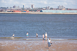 People paddling in the sea at New Brighton Beach looking across the Mersey river estuary to the Liverpool docks England,