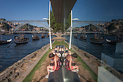 A symmetrical reflection of afternoon sunbathers realaxing on the bank of the Douro river with the panorama of the Ponte de Dom Luis I bridge and the city of Porto behind, on 20th July, in Porto, Portugal. The Dom Luís I (or Luiz I) Bridge is a double-decked metal arch bridge that spans the Douro River between the cities of Porto and Vila Nova de Gaia in Portugal. At the time of construction its span of 172 m was the longest of its type in the world. (Photo by Richard Baker / In Pictures via Getty Images)