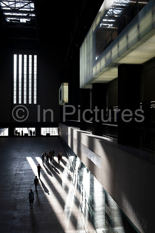 Interior view of evening light falling inside the Turbine Hall at Tate Modern gallery of contemporary art in London, England, United Kingdom. Tate Modern is based in the former Bankside Power Station in Southwark and is one of the largest museums of modern and contemporary art in the world. As with the UKs other national galleries and museums, there is no admission charge for access to the collection displays, which take up the majority of the gallery space. The redevelopment of the space was undertaken by architects Herzog & de Meuron.