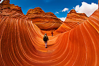 """Hikers exploring """"The Wave"""", a 190 million year old Jurassic-age Navajo sandstone rock formation, Coyote Buttes, Paria Canyon-Vermillion Cliffs Wilderness Area, Utah-Arizona border, USA"""