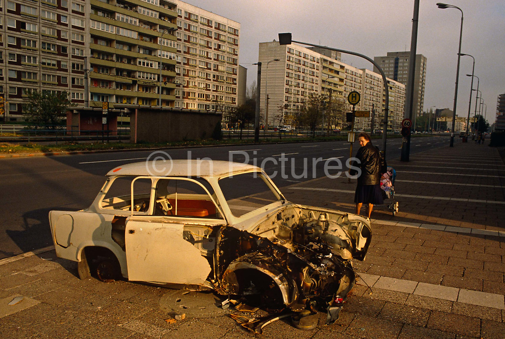 """Taken six months after the fall of the Berlin Wall, a German lady from the old German Democratic Republic (DDR or GDR) looks back over her shoulder nostalgically at an abandoned Trabant car on a sunlit street in eastern Berlin, once in the eastern zone before the Communist-inspired Berlin Wall was breached in November 1989. Blocks of modern East German-designed flats line the street and a tram line can be seen in the middle of the highway. The DDR-produced Trabant suffered poor performance, but its smoky two-stroke engine regarded with affection as a symbol of the more positive sides of East Germany. Many East Germans streamed into West Berlin and West Germany in their Trabants after the opening of the Berlin Wall. It was in production without any significant change for nearly 30 years. The name Trabant means """"fellow traveler"""" in German."""