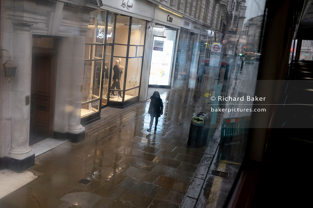 A solitary person walks alone on a wet pavement during seasonal showers on Piccadilly in the capital's West End during the third lockdown of the Coronavirus pandemic, on 22 February 2021, in London, England.