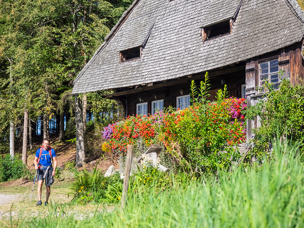 Male hiker passing by typical Black Forest farmhouse, Baden-Wuerttemerg, Germany
