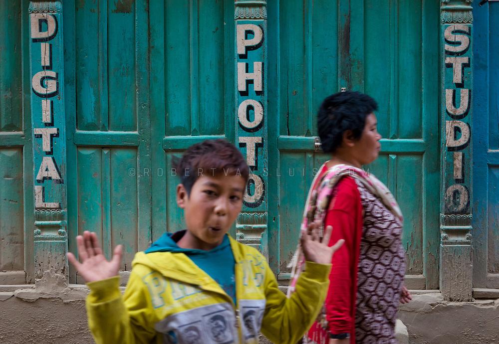 A boy makes a gesture in front of a photo studio in Kathmandu, Nepal. Photo © robertvansluis.com