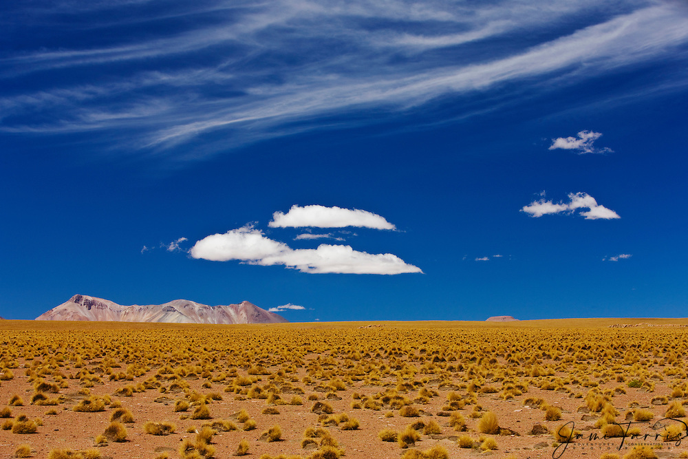 A cloud sits over a small desert mountain on the Altiplano in the Sud Lipez district of Bolivia, Bolivia,South America