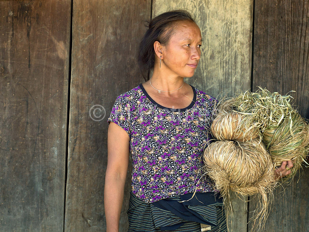 Portrait of Yai with her peeled hemp outside her home in the Hmong village of Ban Pom Khor, Houaphan province, Lao PDR. Making hemp fabric is a long and laborious process; the end result is a strong durable cloth with qualities similar to linen which the Hmong women make into skirts for their traditional clothing. In Lao PDR, hemp is now only cultivated in remote mountainous areas of the north.