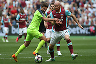 Adam Lallana of Liverpool (L) looks to go past  James Collins of West Ham United (R). Premier league match, West Ham Utd v Liverpool at the London Stadium, Queen Elizabeth Olympic Park in London on Sunday 14th May 2017.<br /> pic by Steffan Bowen, Andrew Orchard sports photography.