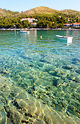 View across the Brna bay with light reflections in the water. Very clear water so you can see the rock formations at the bottom, translucent. Boats moored at a buoy. Mountains in the background. Prizba village. Korcula Island. Prizba, Riva Apartments, Danny Franulovic. Korcula Island. Dalmatian Coast, Croatia, Europe.