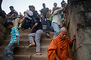 A Buddhist monk joins tourists climbing down the steep steps from the top of Phnom Bakheng, where people gather at sundown to watch the sun set over the surrounding green fields. Phnom Bakheng was the first monument to be built in the Angkor area, constructed as a temple-mountain and hewn out of the rock in 889 by Yasovarman I it has great views all the way to Tonle Sap lake.