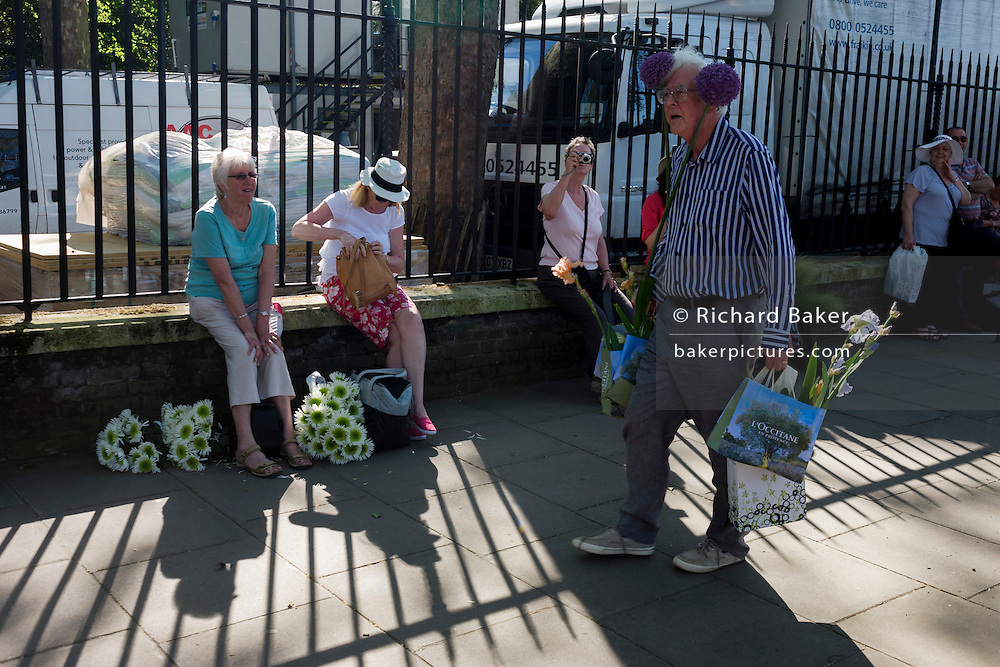 Visitors to the RHS Chelsea Flower Show make their way home through local streets after the last day's plant sell-off.
