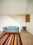 Interior of a modern house, hall with divan and striped rug