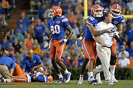 Florida head coach Jim McElwain is restrained by tight end DeAndre Goolsby (30) and offensive lineman Fred Johnson (74) when McElwain showed his displeasure after quarterback Luke Del Rio, left, was knocked out of the game on a roughing the passer penalty during the second half of an NCAA college football game against North Texas in Gainesville, Fla., Saturday, Sept. 17, 2016. (AP Photo/Phelan M. Ebenhack)