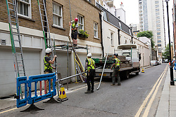 © Licensed to London News Pictures. 27/06/2014. London, UK. Scaffolding is removed from the garage of a mews house in Harriet Walk, Knightsbridge in London on 27th June 2014, where a man yesterday reversed a Porsche 4x4 trapping and severing his arm in the scaffolding and suffering head injuries. Photo credit : Vickie Flores/LNP