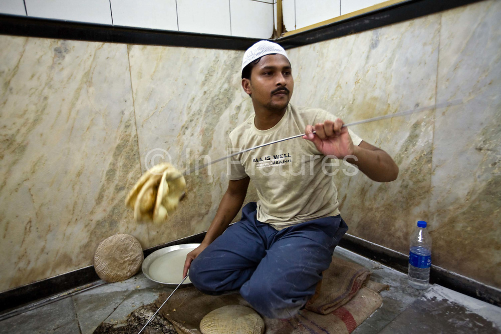 L M Rahman throws fresh naan bread from the tandoor to a a waiter at Karim's Restaurant, Delhi, India<br /> Karim's is a Delhi landmark was started by Haji Karimuddin who decided to open a restuarant catering to people coming to Delhi for the Coronation Durbar in 1911