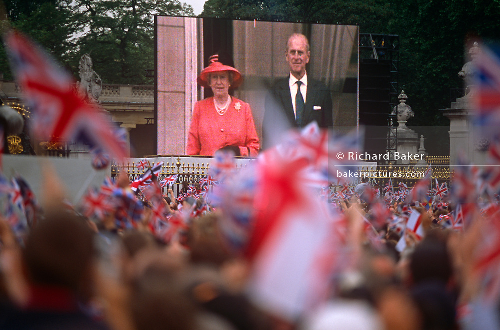 Queen Elizabeth and husband Prince Phillip are televised from the balcony of Buckingham Palace on to a giant screen for the crowds below, during the monarch's Golden Jubilee celebrations, on 3rd June 2002, in London, England.
