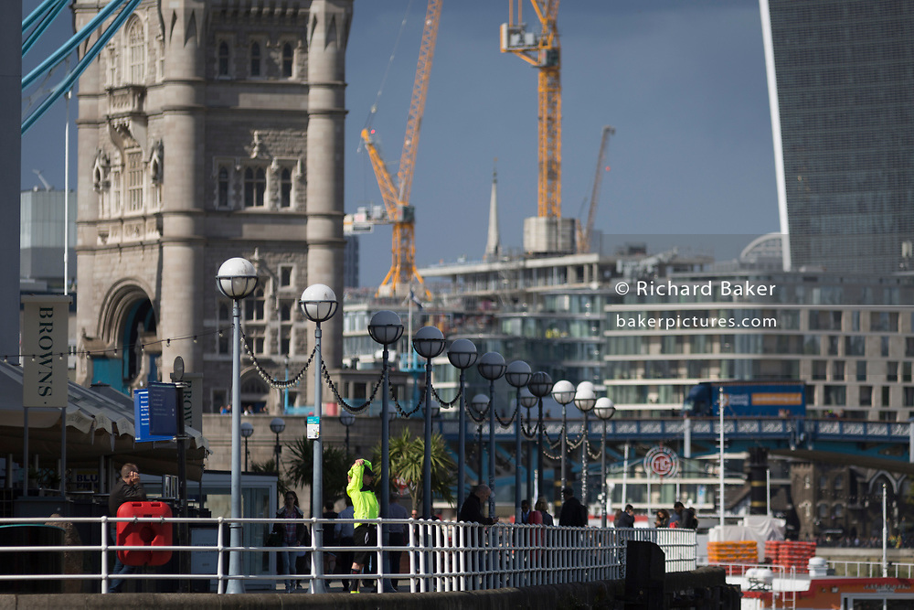 A runner wearing hi-vis colours stretches after exercising beneath the south main tower of the Victorian-era Tower Bridge on the capital's Butler's Wharf, on 14th September 2017, in London, England.