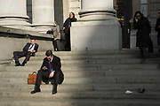 City workers break sitting on the steps of the Guardian Royal Exchange Building. The financial district. The City of London, UK.