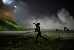 © Licensed to London News Pictures. 23/10/2016. Calais, France. A young migrant throws a rock at French police on the eve of the demolition of the camp. French authorities have given an eviction order to thousands of refugees and migrants living at the makeshift living area of the French coast. Photo credit: Ben Cawthra/LNP