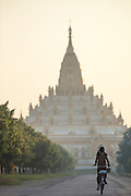 Young girl riding bicycle towards Swe Taw Myat Pagoda, Mandalay