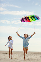 Two sisters run on the beach with a colorful kite in the sky above them.
