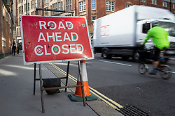 © Licensed to London News Pictures. 09/10/2019. London, UK. A commuter walks past a road ahead closed sign in Westminster on the third day of protests by Extinction Rebellion . Police continue to attempt to clear roads in the borough.  Photo credit: George Cracknell Wright/LNP