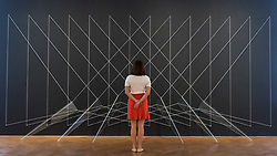 """© Licensed to London News Pictures. 25/06/2018. LONDON, UK. A staff member views an artwork by Lydia Okumura. Preview of """"Lands of Lads, Land of Lashes"""", an exhibition of sculptures and paintings by three female artists of the1960s and 1970s - Rosemarie Castoro, Wanda Czelkowska and Lydia Okumura - specialising in Minimal and Post-Minimal art.  The exhibition, held at Galerie Thaddaeus Ropac in Mayfair, runs 25 June to 11 August 2018.  Photo credit: Stephen Chung/LNP"""