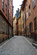 Vertical photo of an empty side street in the Old Town section of Stockholm.