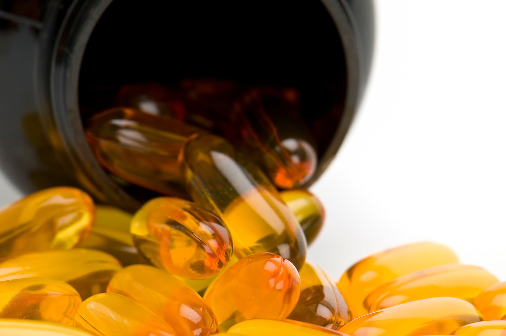 Close up view of Omega 3 pills, spilling from bottle. Use of selective focus.