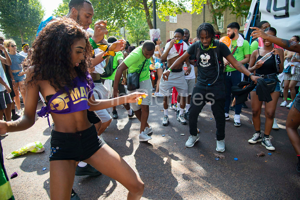 Party goers dancing at the Notting Hill Carnival, on 25th August, 2019 in London, United Kingdom. One million people are expected on the streets in scorching temperatures for the Notting Hill Carnival, Europes largest street party and a celebration of Caribbean traditions.