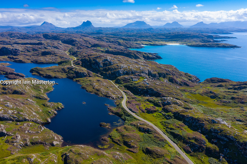 Aerial view of mountains and single track road part of North Coast 500 in Assynt Coigach region of Scottish Highlands, Scotland, UK