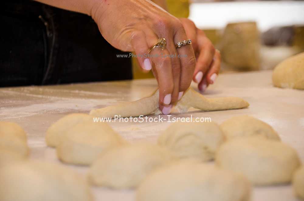 close up of the Hands of a female pastry chef as she demonstrates how to  knead, roll and shape  dough at a baking workshop