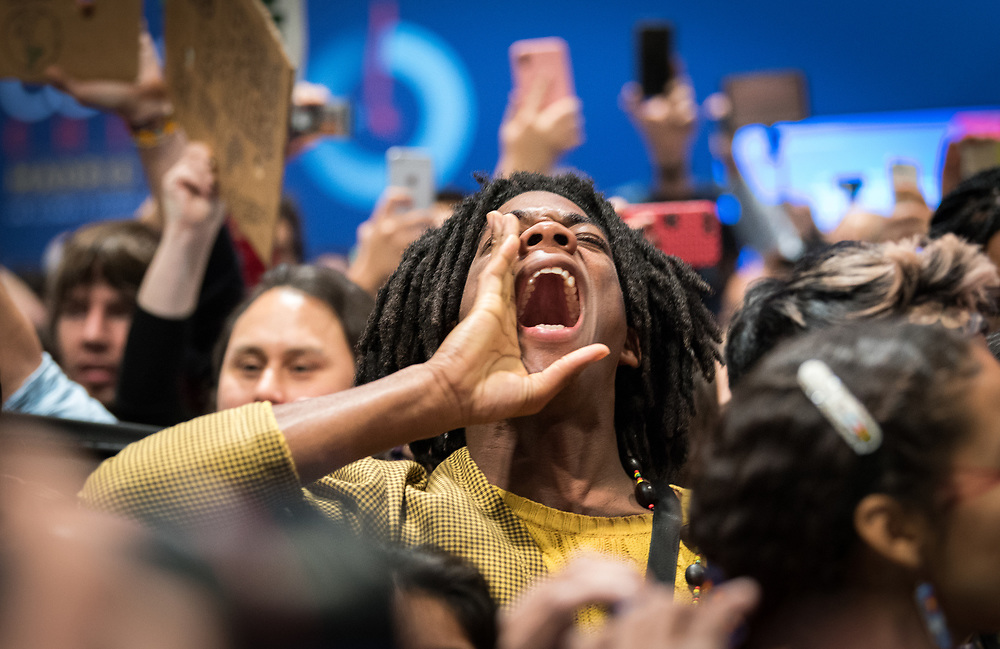11 December 2019, Madrid, Spain: A man calls out for justice, as hundreds of civil society and other actors hold an unauthorized protest outside the plenary hall of COP25 in Madrid, to draw attention to the failures of the climate talks and to call on rich countries to step up and pay up for real solutions, and to highlight the threat of loopholes, false solutions like carbon markets, and the need for those who caused the climate crisis to pay up for loss and damage while respecting human rights.