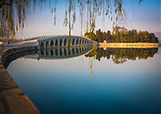 """The Summer Palace (Chinese: 頤和園), is a vast ensemble of lakes, gardens and palaces in Beijing. It was an imperial garden in the Qing Dynasty. Mainly dominated by Longevity Hill (万寿山; 萬壽山) and Kunming Lake, it covers an expanse of 2.9 square kilometres, three-quarters of which is water.<br /> <br /> Connecting the eastern shore of Kunming Lake and Nanhu Island in the west, the Seventeen-Arch Bridge was built during the reign of Emperor Qianlong (1711-1799). There are some thirty bridges in the Summer Palace and this is the largest one, with a length of 150 meters (164 yards) and a width of 8 meters (8.75 yards). It is not only the sole passageway to Nanhu Island, but also an important attraction in the lake area. <br /> <br /> In December 1998, UNESCO included the Summer Palace on its World Heritage List. It declared the Summer Palace """"a masterpiece of Chinese landscape garden design. The natural landscape of hills and open water is combined with artificial features such as pavilions, halls, palaces, temples and bridges to form a harmonious ensemble of outstanding aesthetic value""""."""