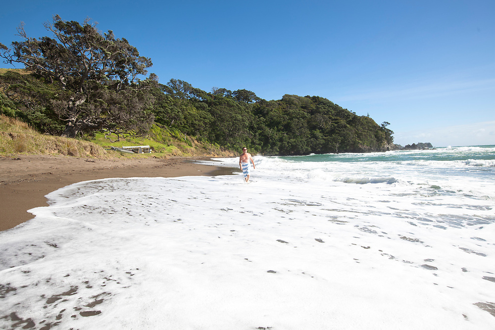 Man walking alongside the tide washing at Moureeses Bay, East Coast, Far North, New, Zealand.