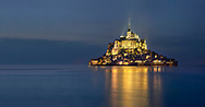 """Scenic view of the tidal island  of Mont Saint Michel at night at high tide surrounded and its medieval abbey of Saint Michel. Normandy France.<br /> <br /> The tides vary greatly, at roughly 14 metres (46 ft) between highest and lowest water marks. Popularly nicknamed """"St. Michael in peril of the sea"""" by medieval pilgrims making their way across the flats, the mount can still pose dangers for visitors who avoid the causeway and attempt the hazardous walk across the sands from the neighbouring coast."""